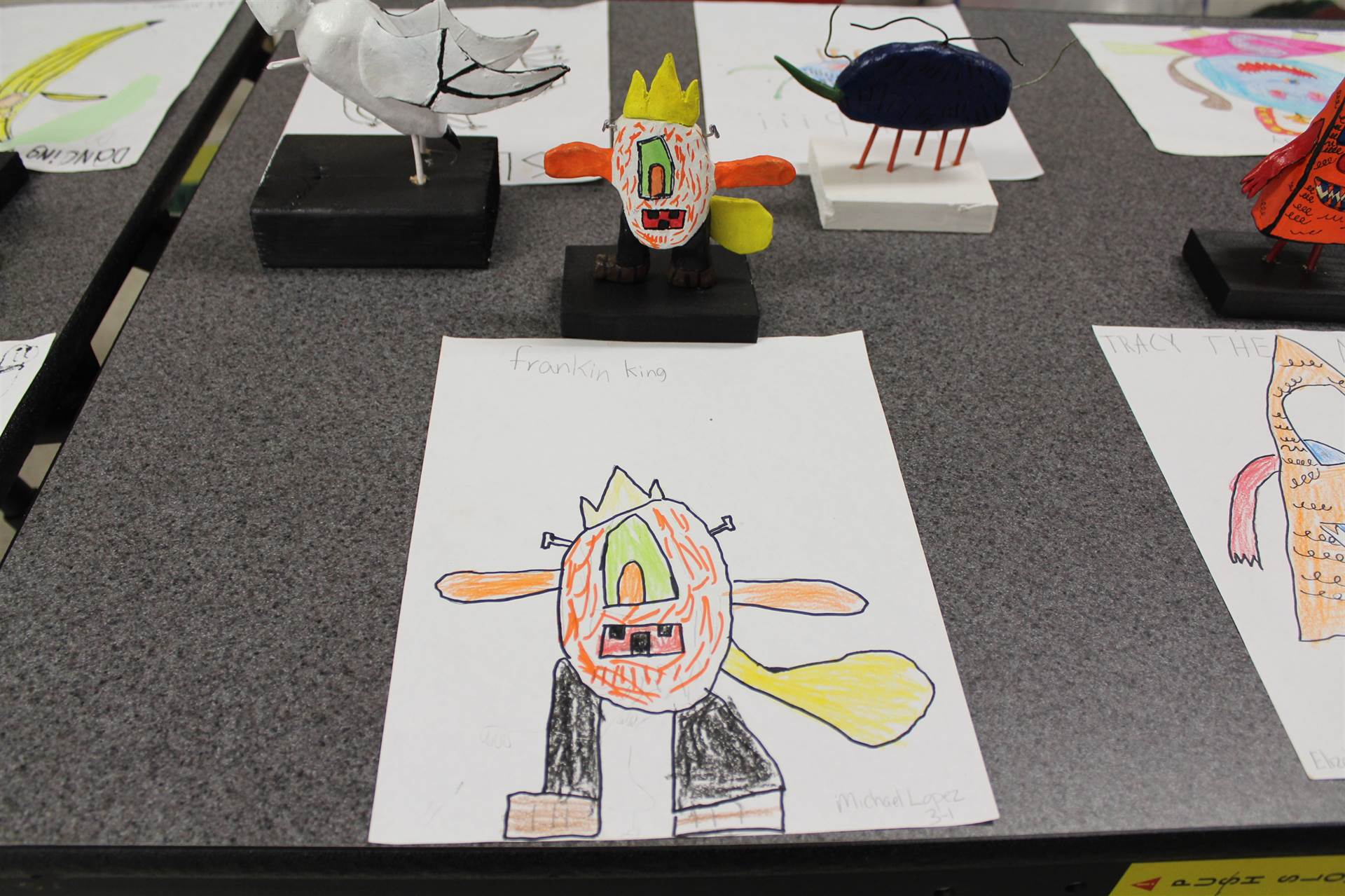 monster 3 d sculpture next to drawn picture 15