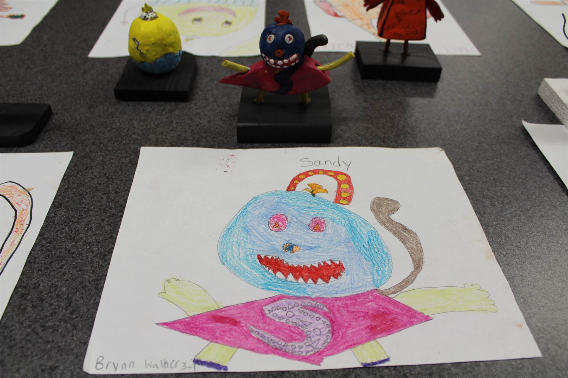 monster 3 d sculpture next to drawn picture 9