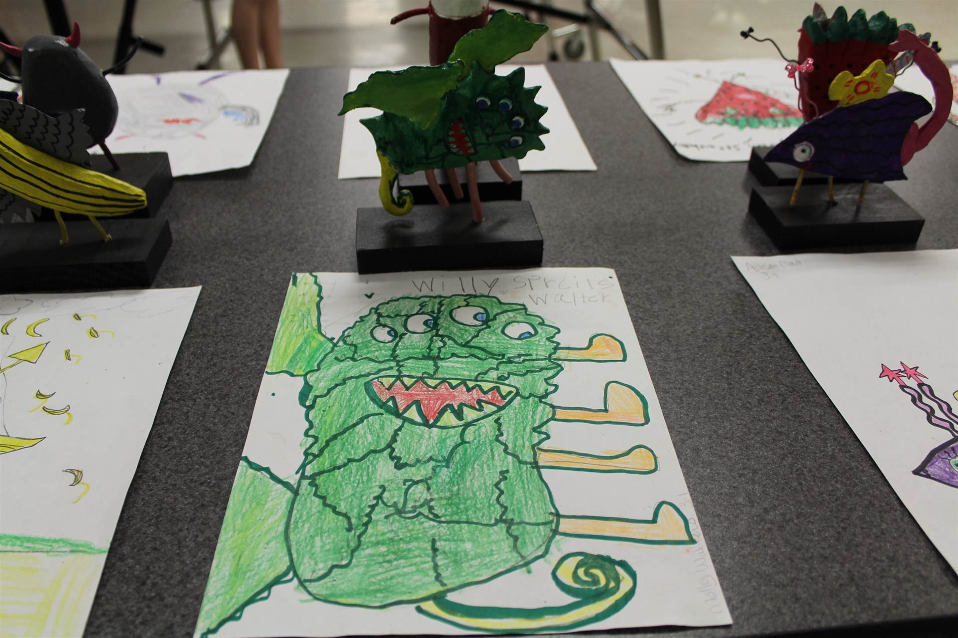 monster 3 d sculpture next to drawn picture 4.