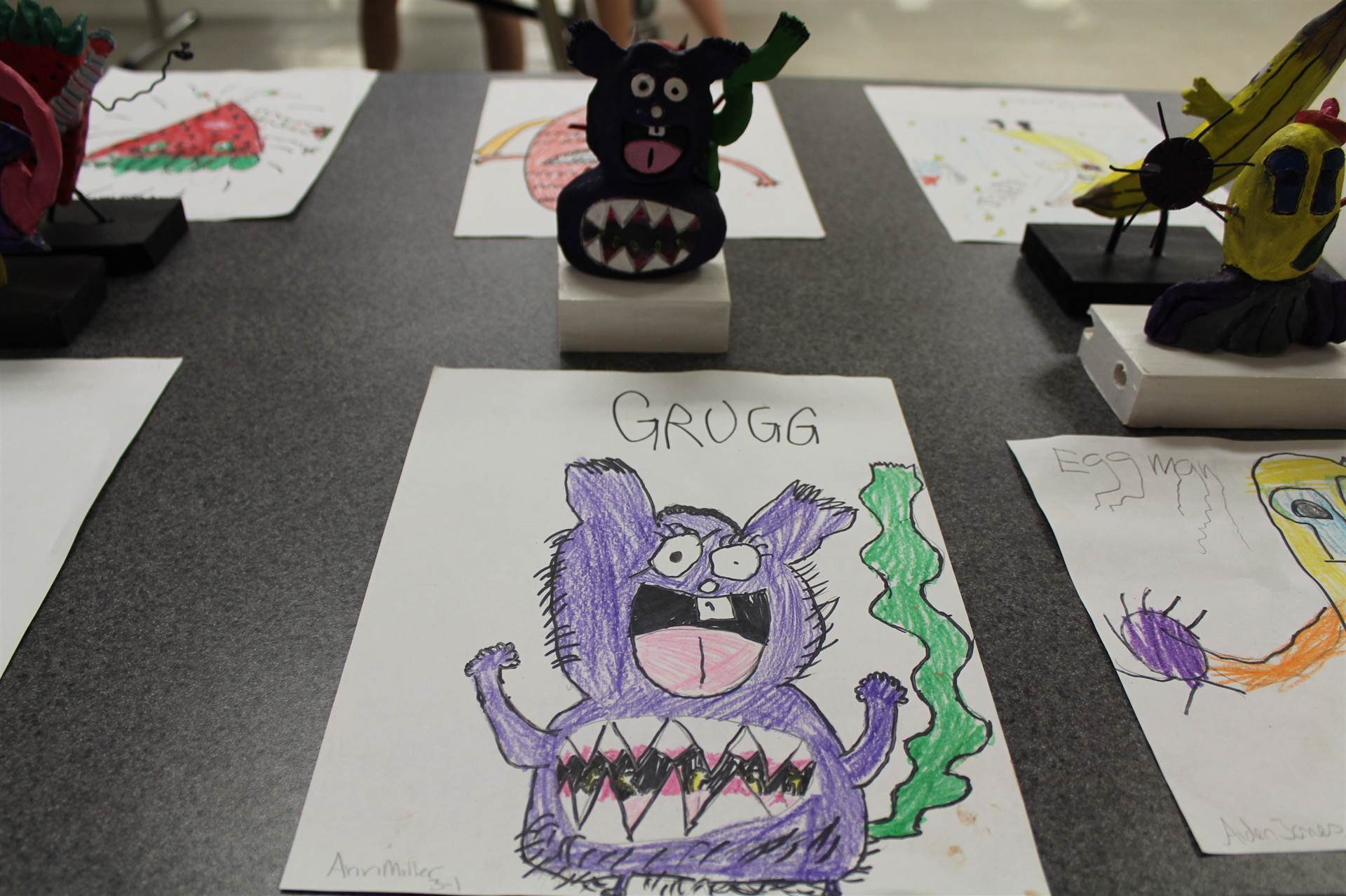 monster 3 d sculpture next to drawn picture 2