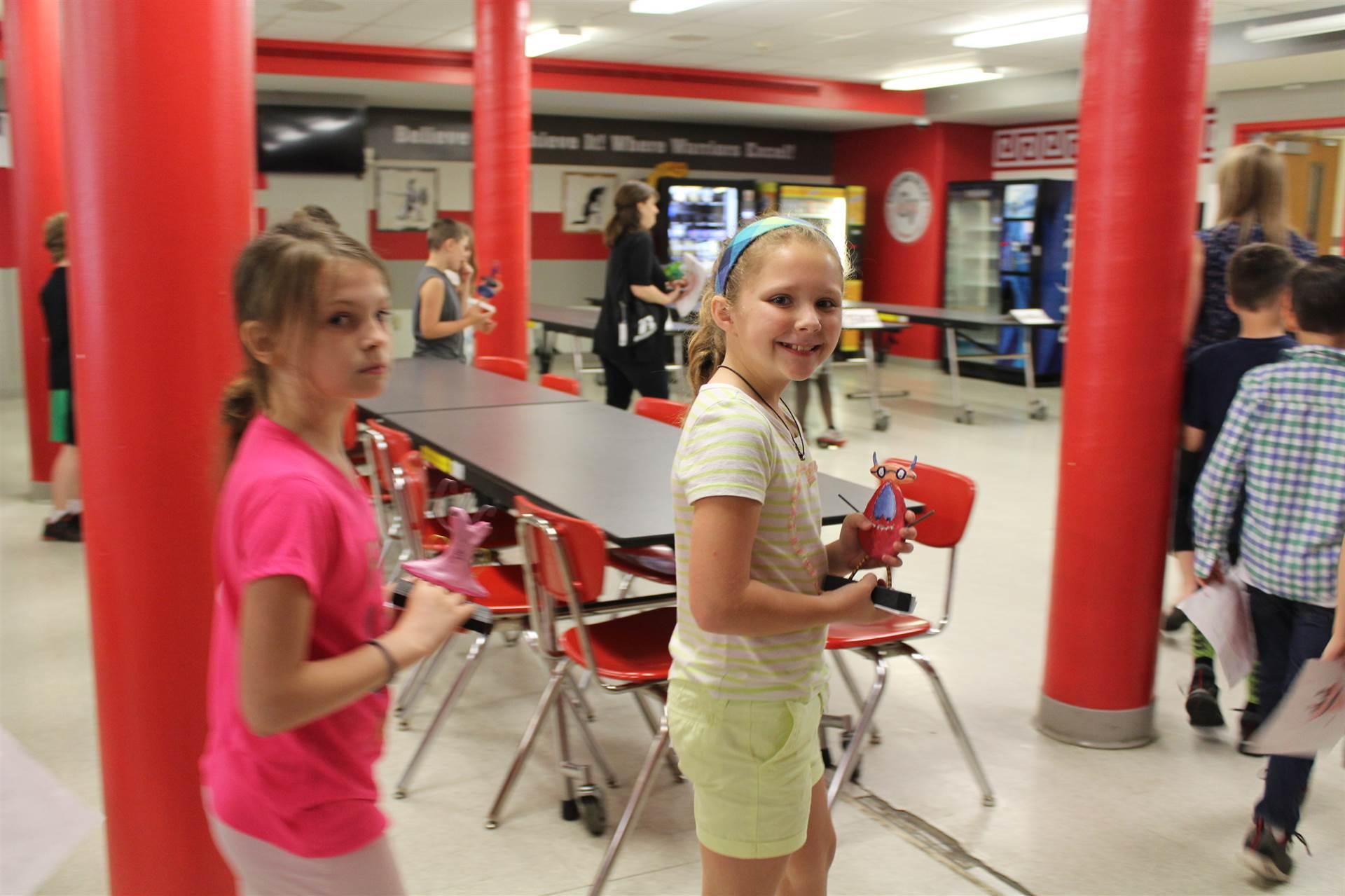 girls walk away smiling holding 3 d sculpture