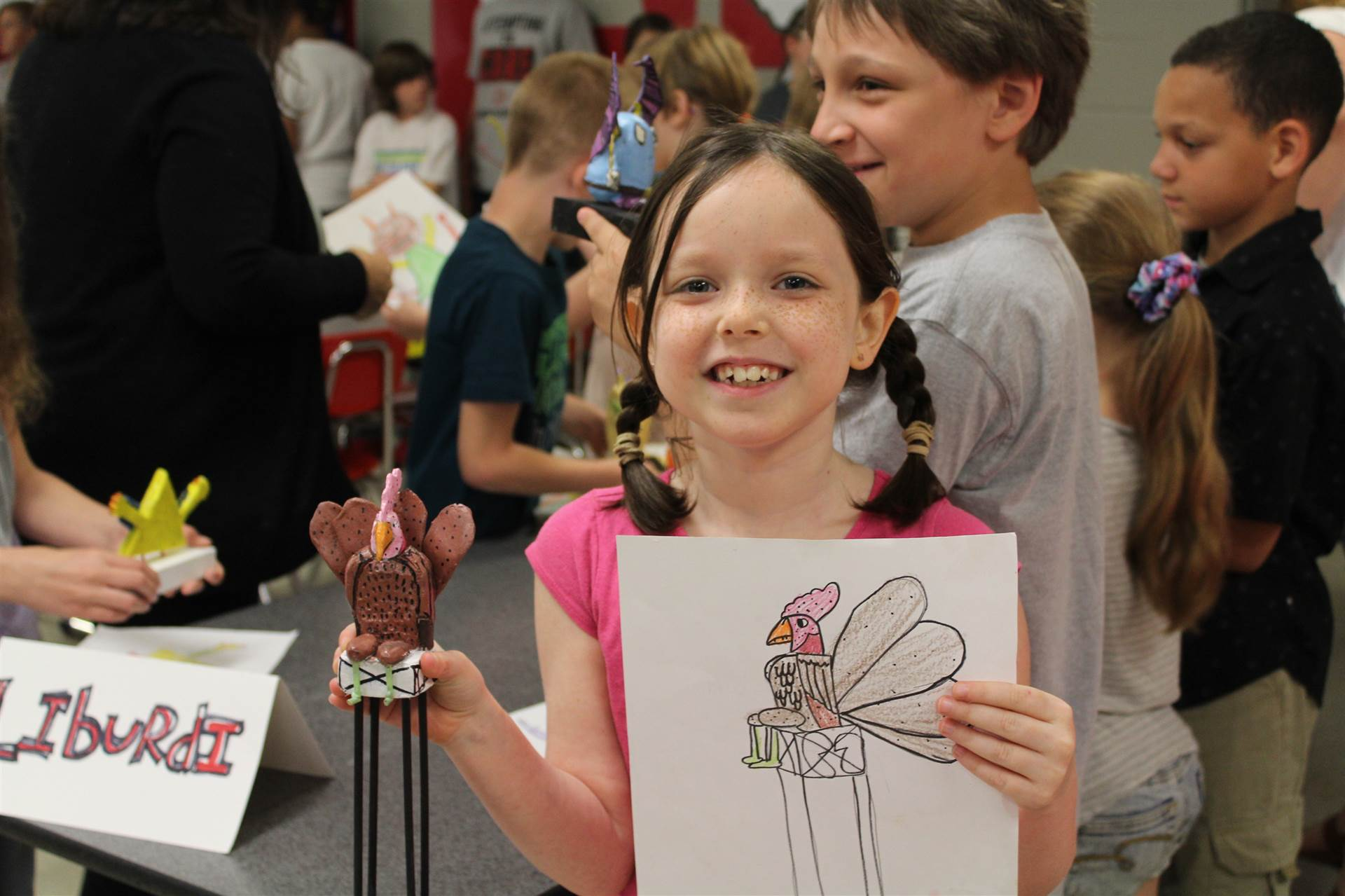 girl holds her drawing in one hand and the monster mash 3 d creation in other hand smiling