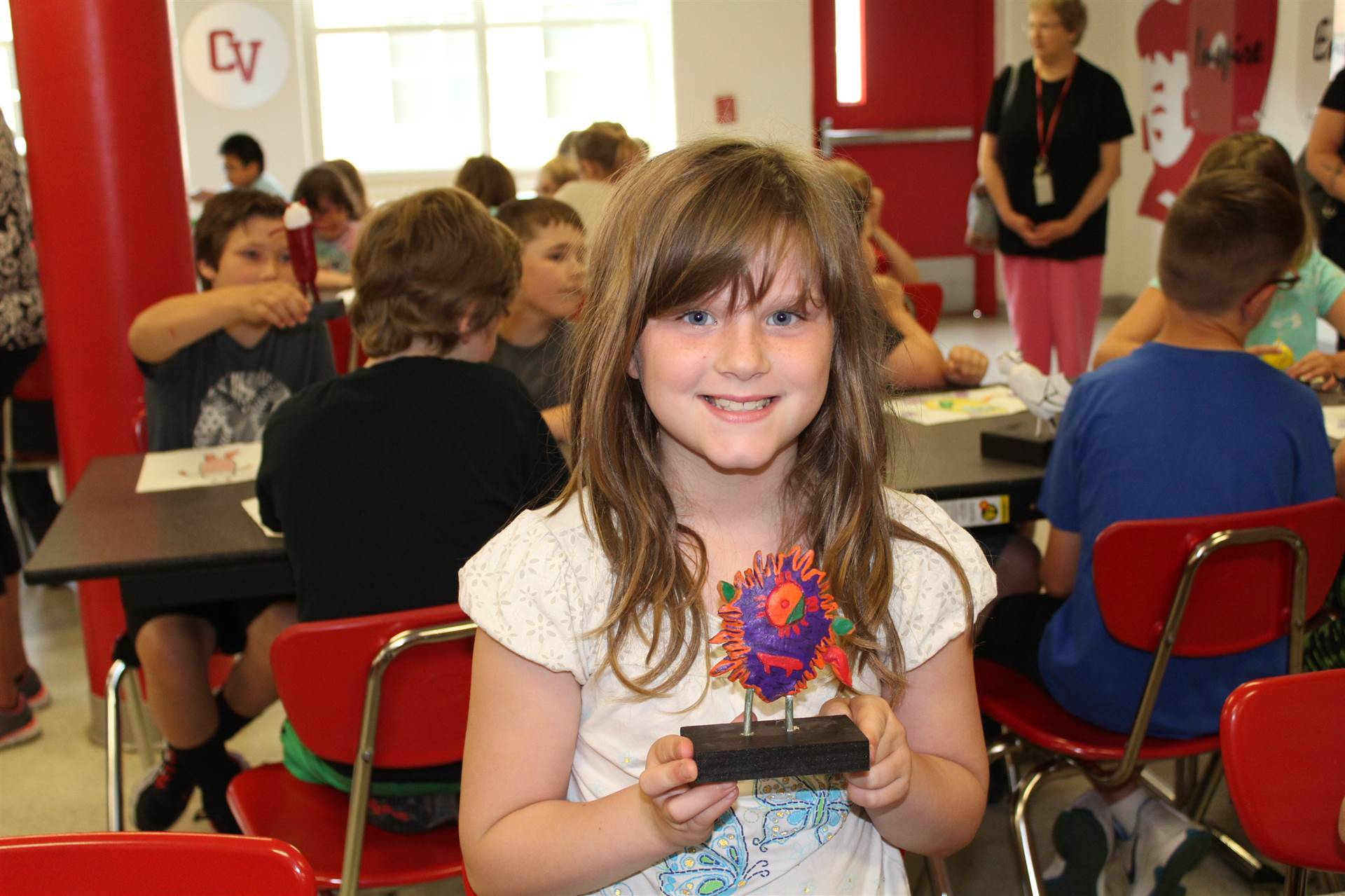 girl smiles at cafeteria table holding 3 d monster sculpture in her hands