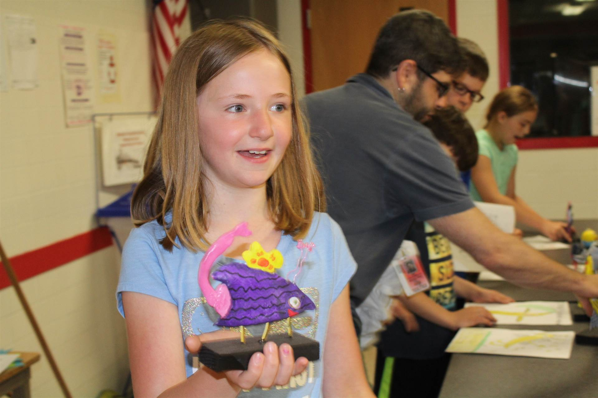 girl in blue shirt from sixth table smiles holding 3 d monster mash reveal sculpture