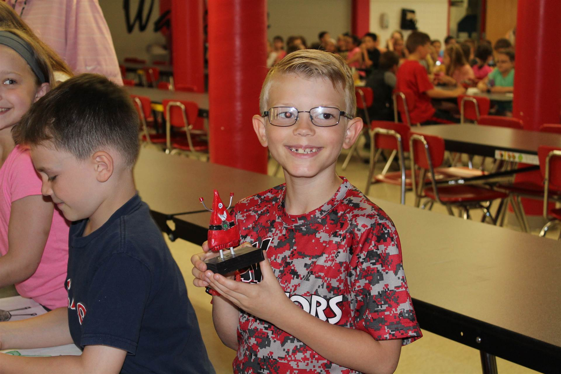 boy smiles with his red 3 d monster sculpture in hand.