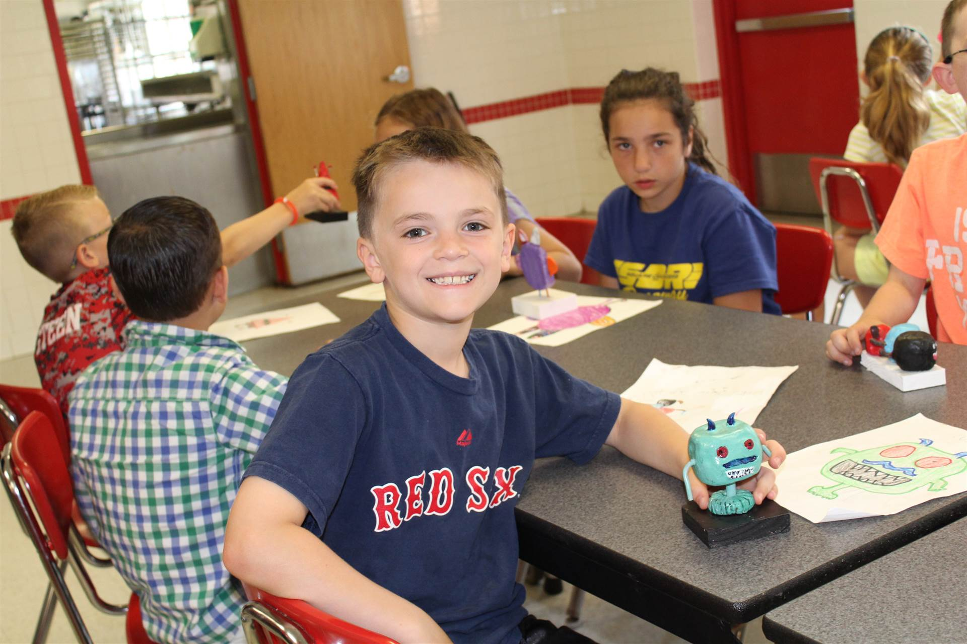 boy smiles sitting with 3 d monster sculpture in one hand on the cafeteria table