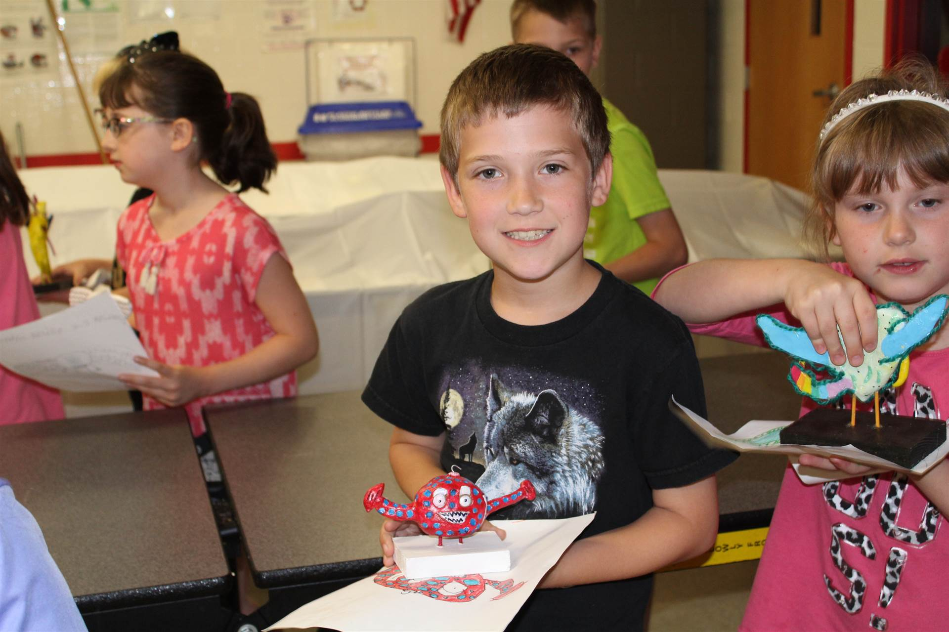 boy in wolf shirt smiles holding his drawing and new 3 d monster sculpture