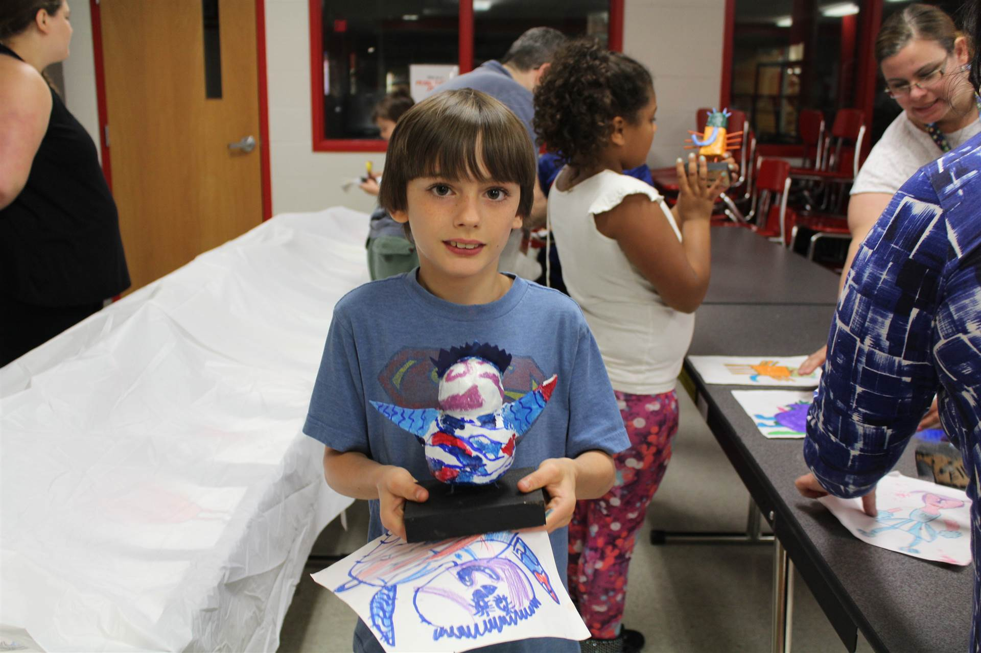 boy in blue shirt smiles holding drawing and 3 d sculpture