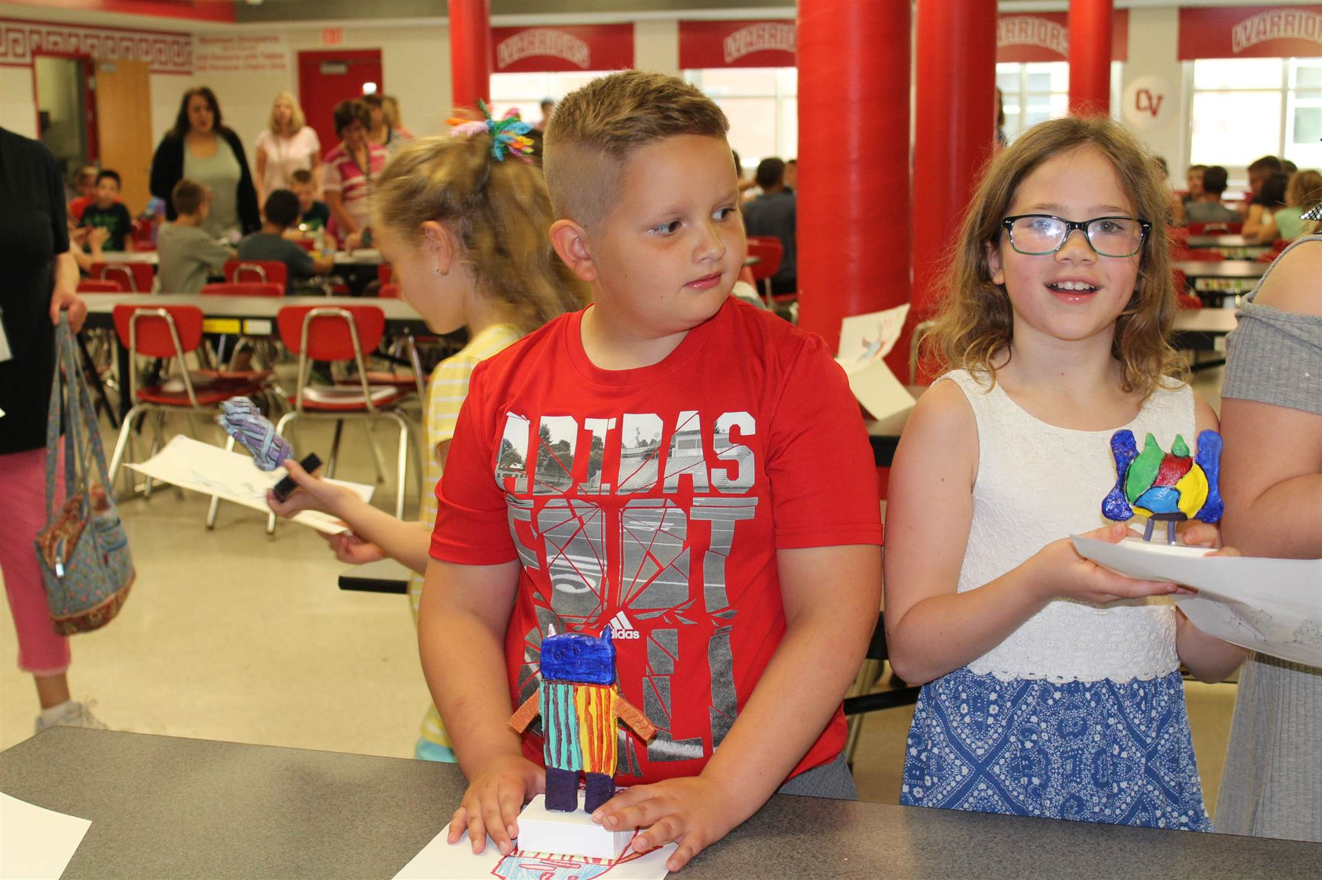 boy and girl with their new 3 d monster mash reveal sculptures.