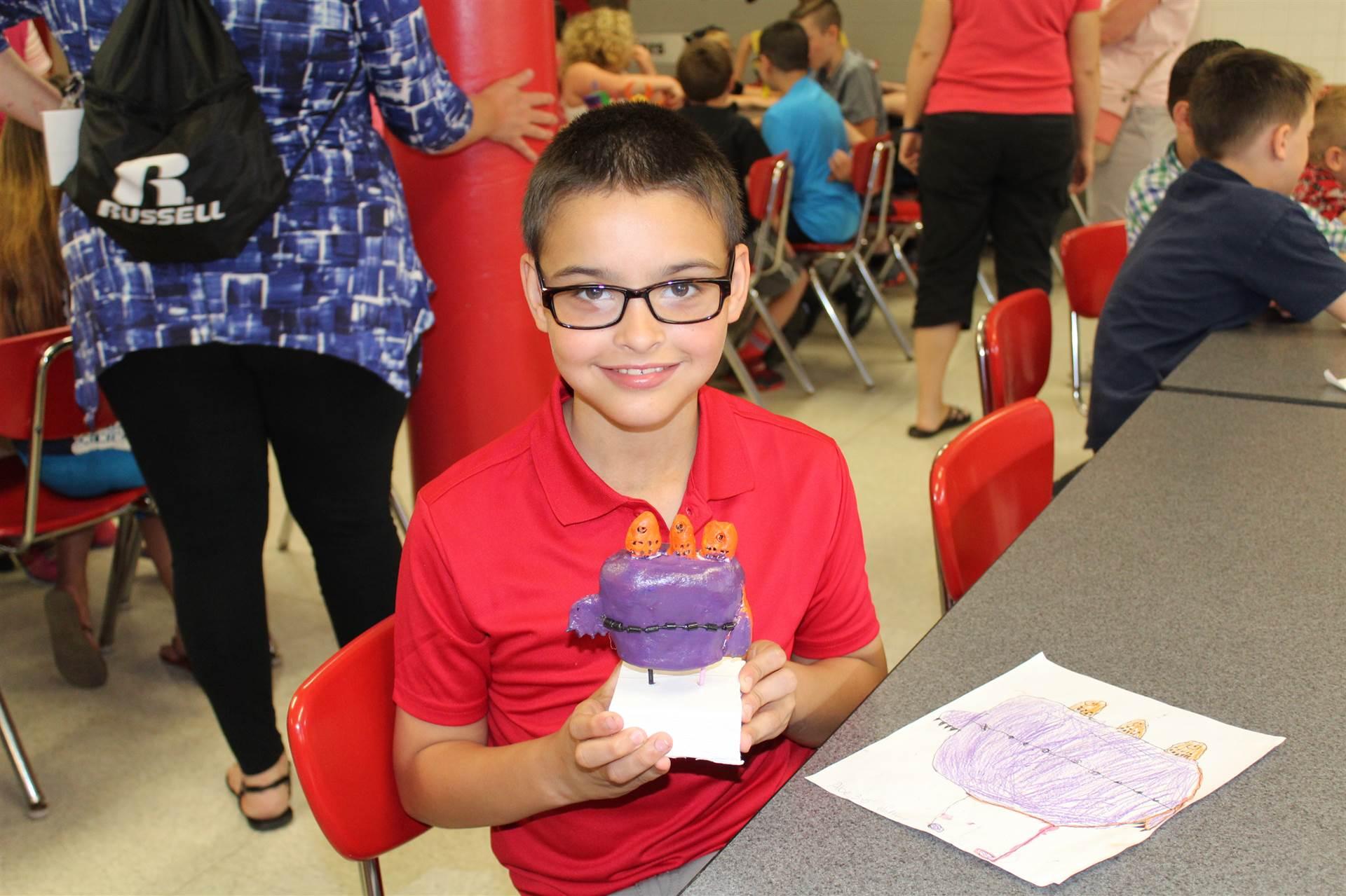 boy sitting smiling holding 3 d monster sculpture in both hands