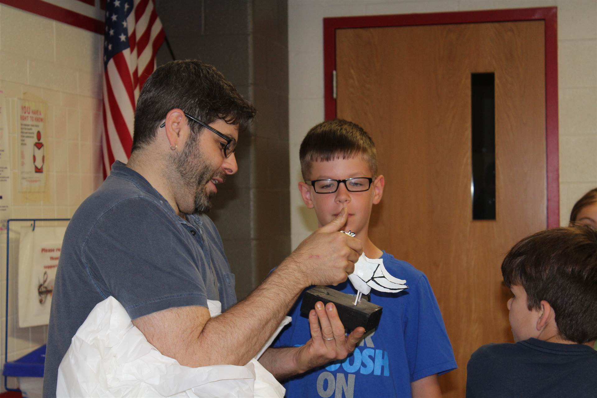 mr fitzsimmons talks to third grade student about his sculpture