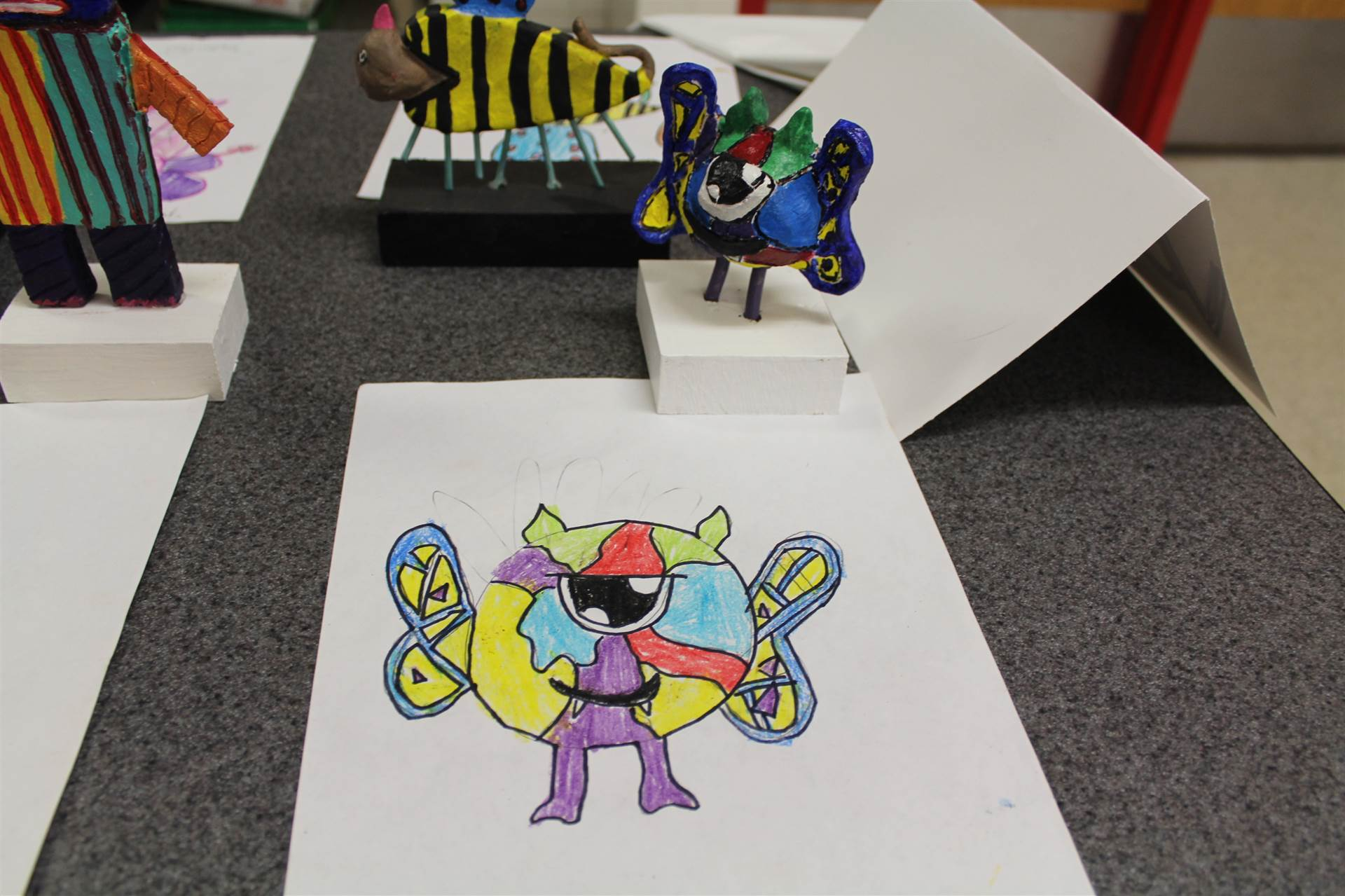 monster 3 d sculpture next to drawn picture 130