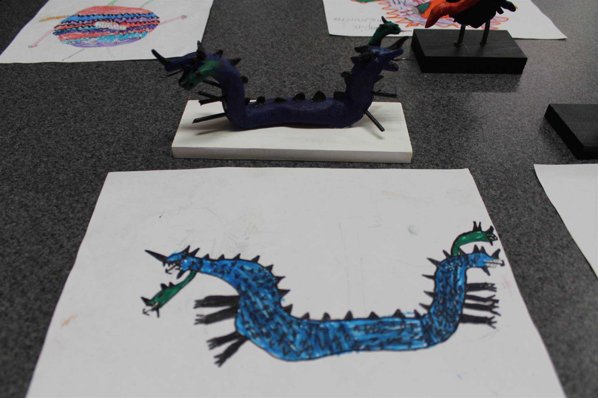 monster 3 d sculpture next to drawn picture 125