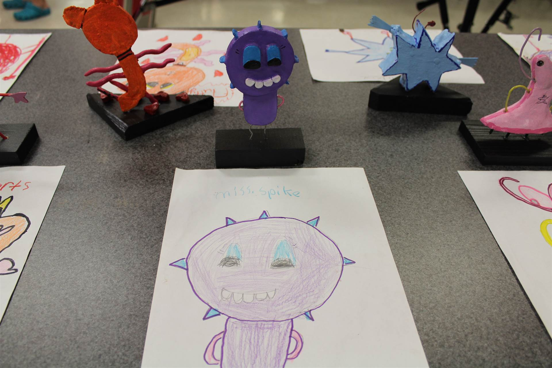 monster 3 d sculpture next to drawn picture 103