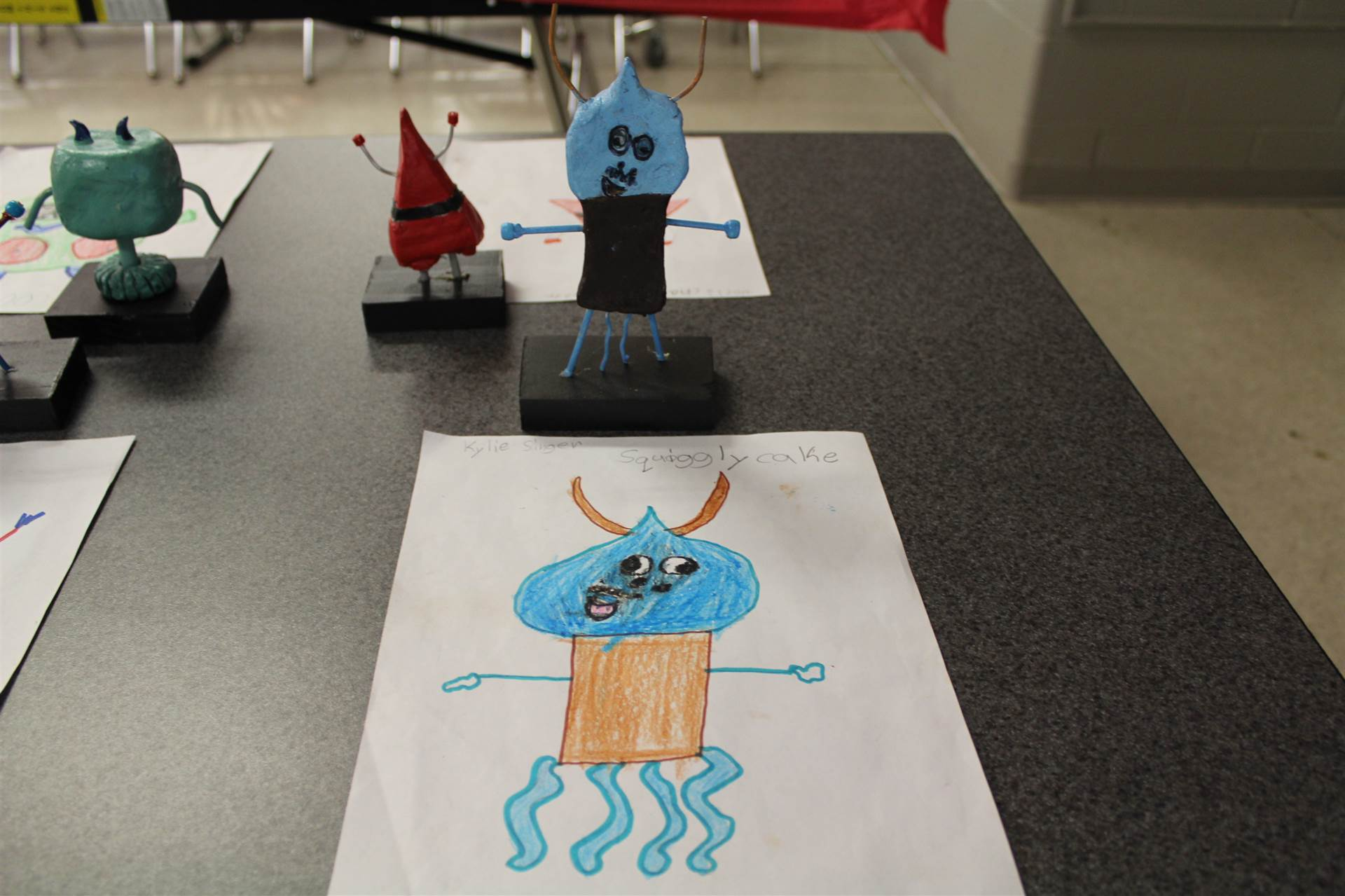 monster 3 d sculpture next to drawn picture 96