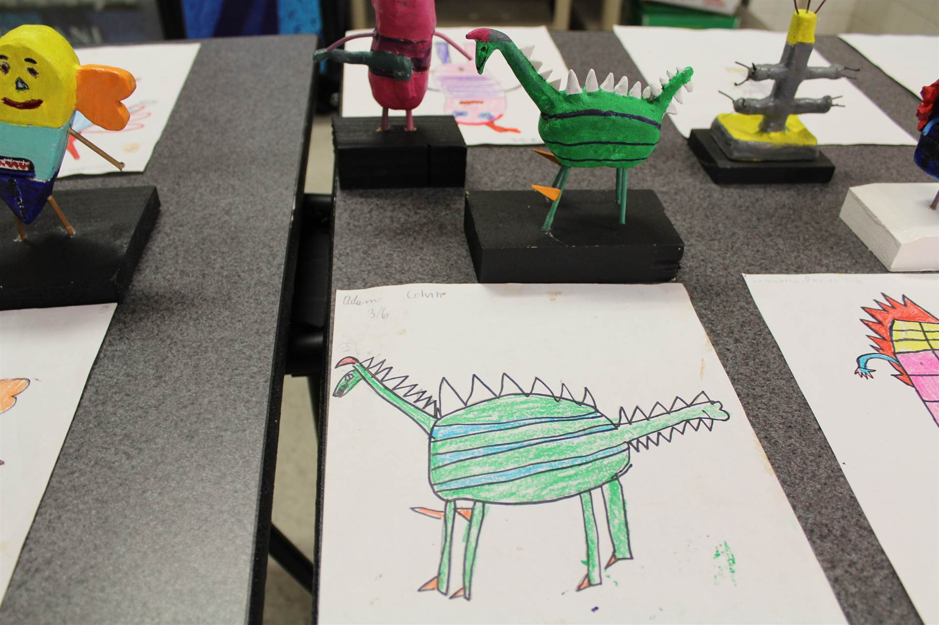 monster 3 d sculpture next to drawn picture 108