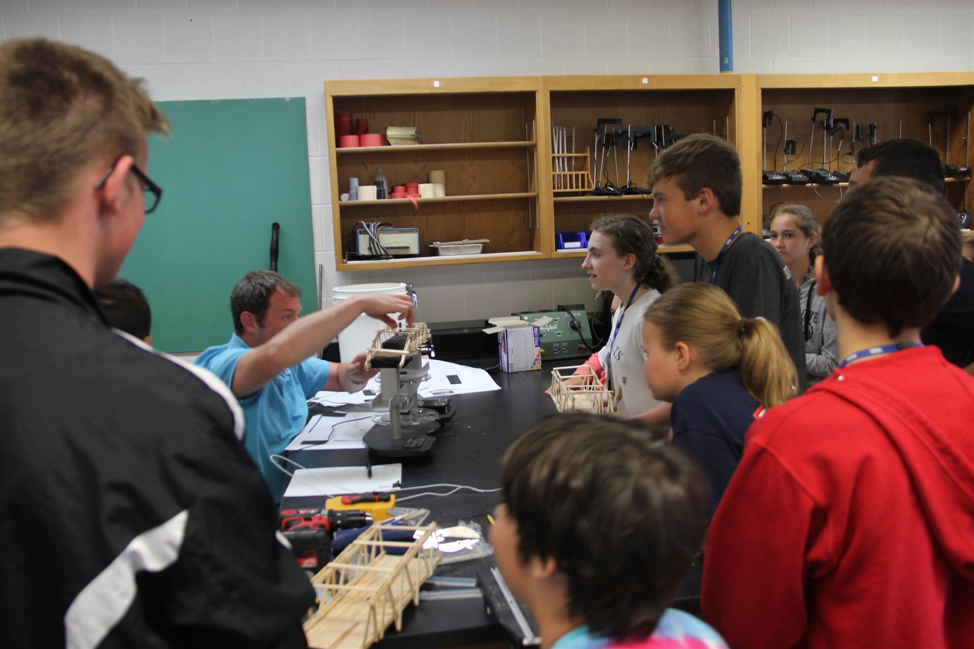 students watch test of how much weight bridges made of popsicle sticks can hold