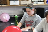c v student writes her equation in boces summer steam academy project.