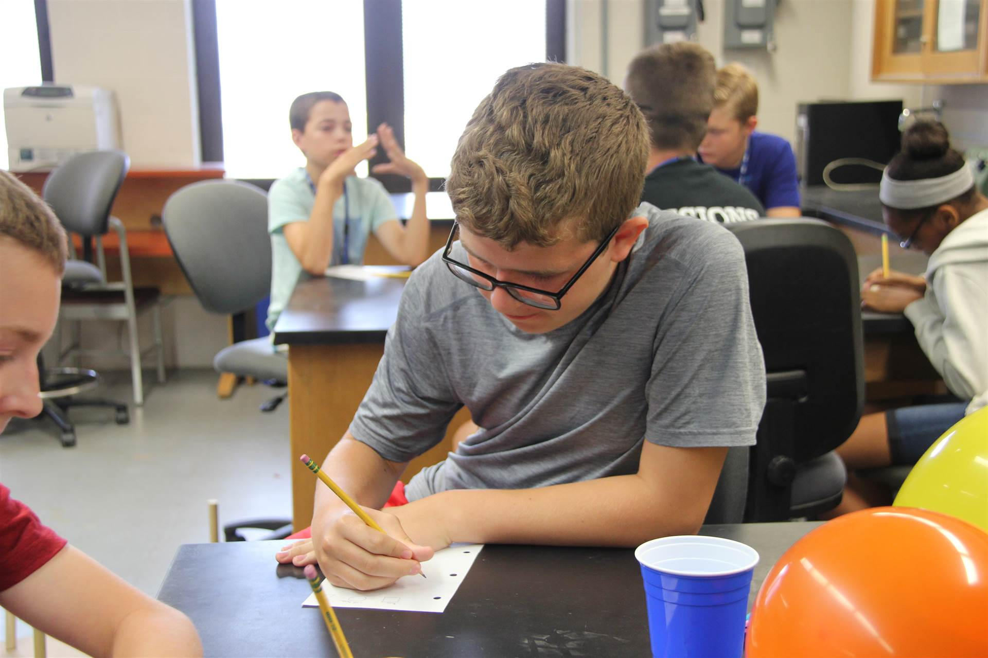 c v student writes out equation at boces summer steam academy
