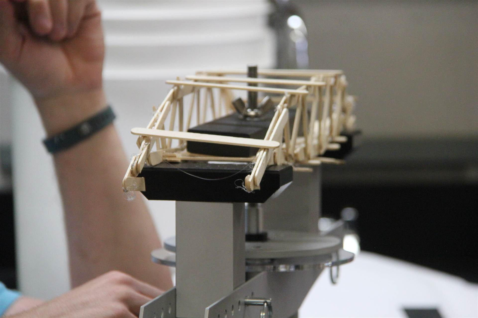 up close shot of bridge made of popsicle sticks going through test of how much weight it can hold