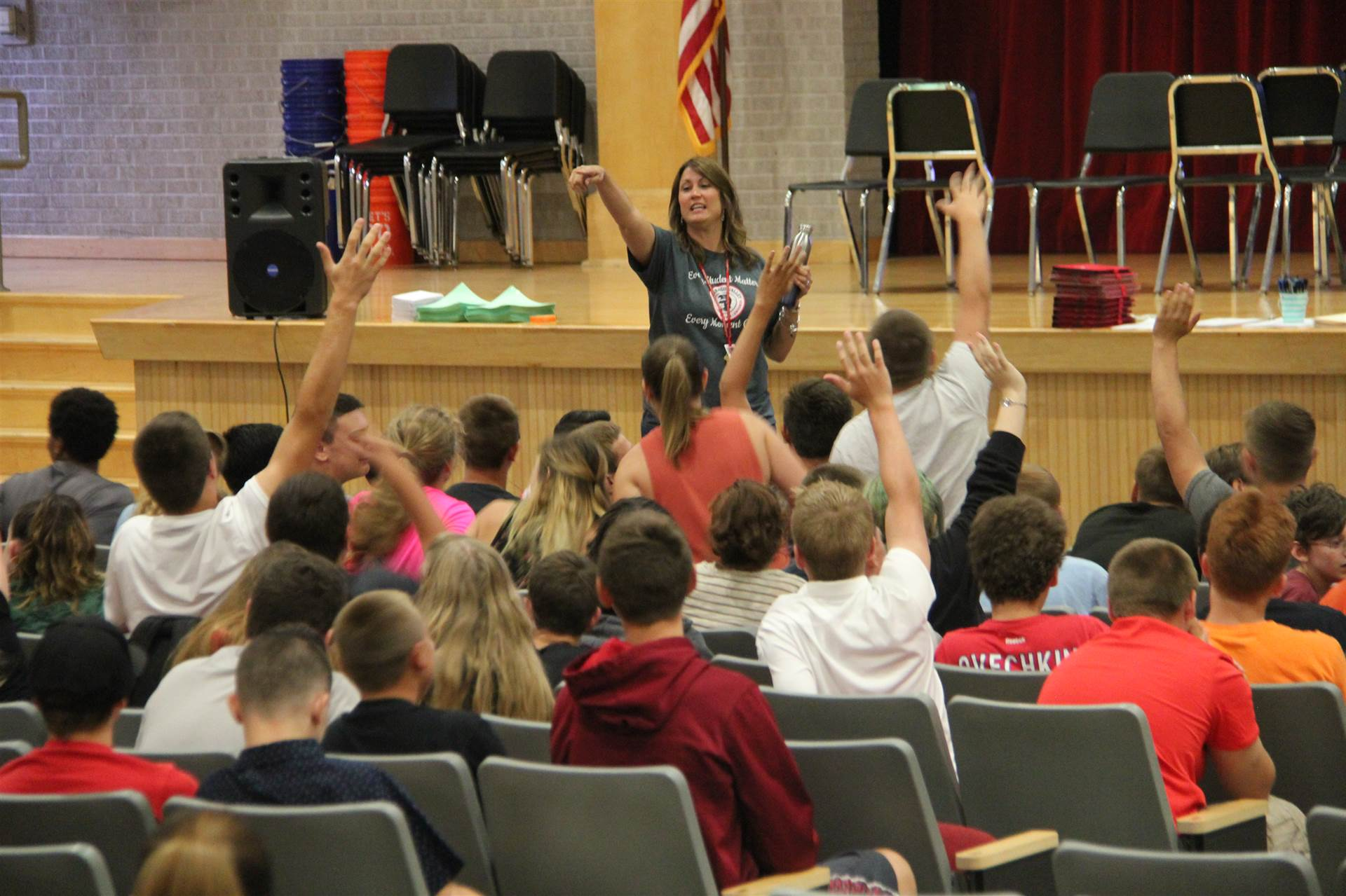 students raise their hands to participate in musical chairs at freshman orientation