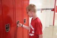student opening his locker at freshman orientation