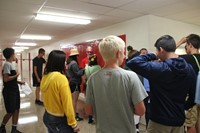 group of students taking part in scavenger hunt at high school locker