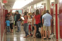 wide shot of sixth grade students opening their new lockers at sixth grade orientation