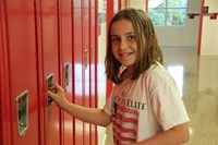 sixth grade student smiles standing next to her new locker at middle school orientation