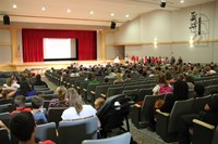 far away shot of principal attleson speaking with sixth grade students parents and guardians in audi
