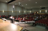 far away shot from front of auditorium of principal attleson speaking with sixth grade students pare