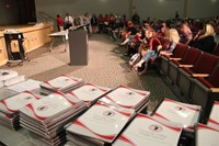 middle school agendas and students parents and guardians in seats at auditorium
