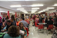 a wide shot from the back of the middle school cafeteria of incoming sixth graders and their parents