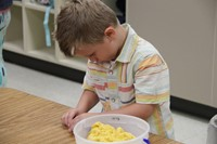 boy builds shapes with yellow clay