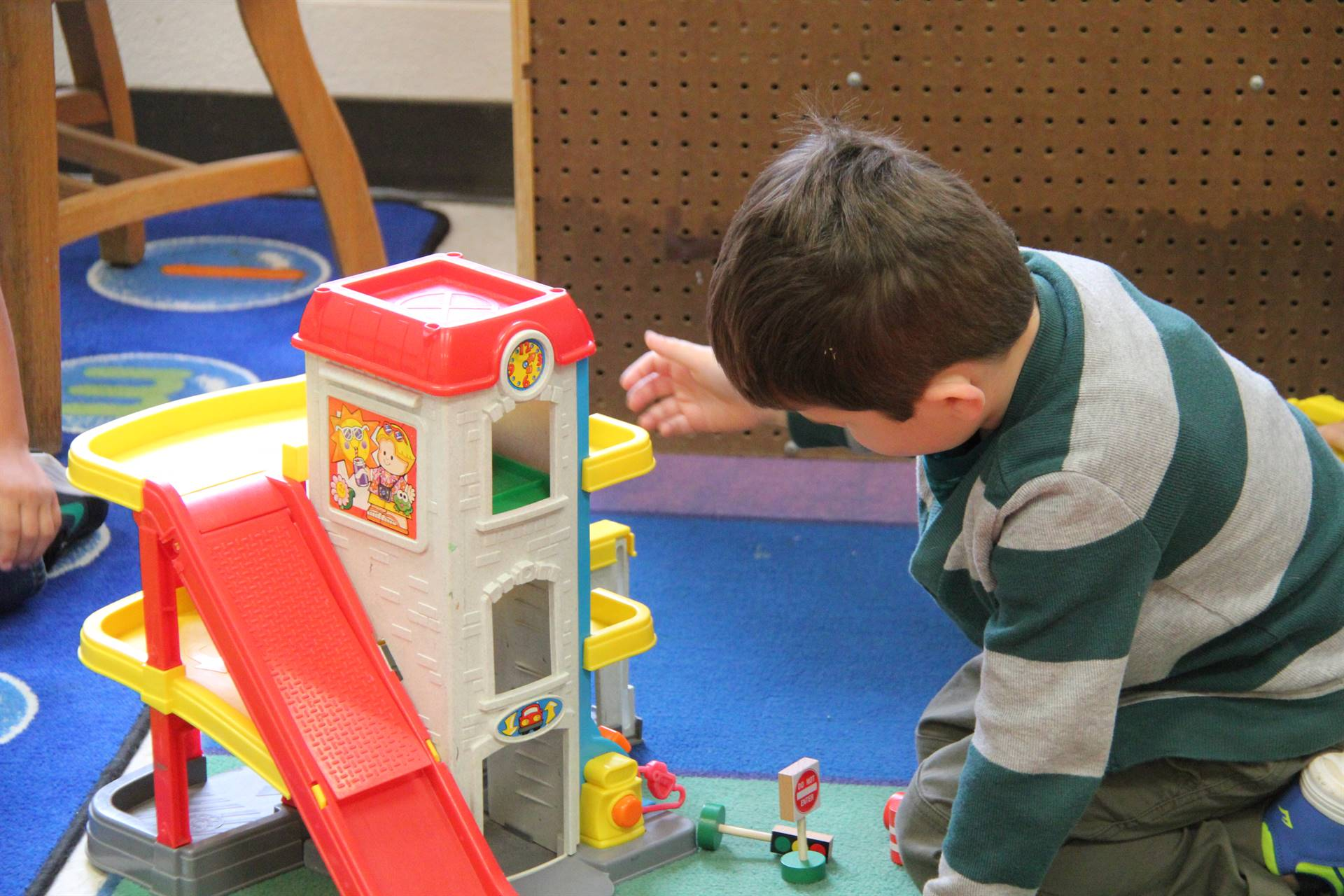 boy plays with toy garage