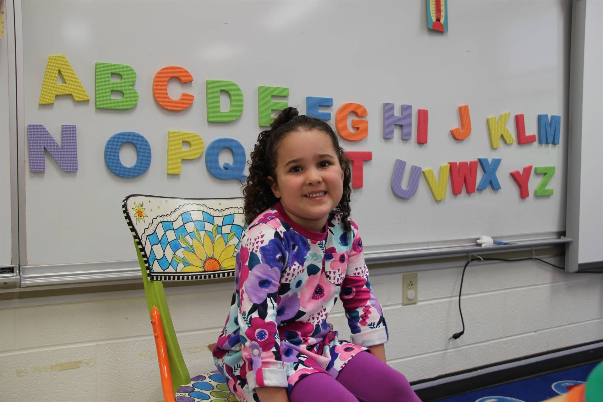 pre k student smiles next to alphabet on first day