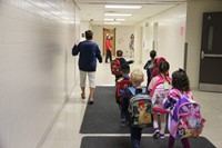 pre k students are led to class on their first day of school