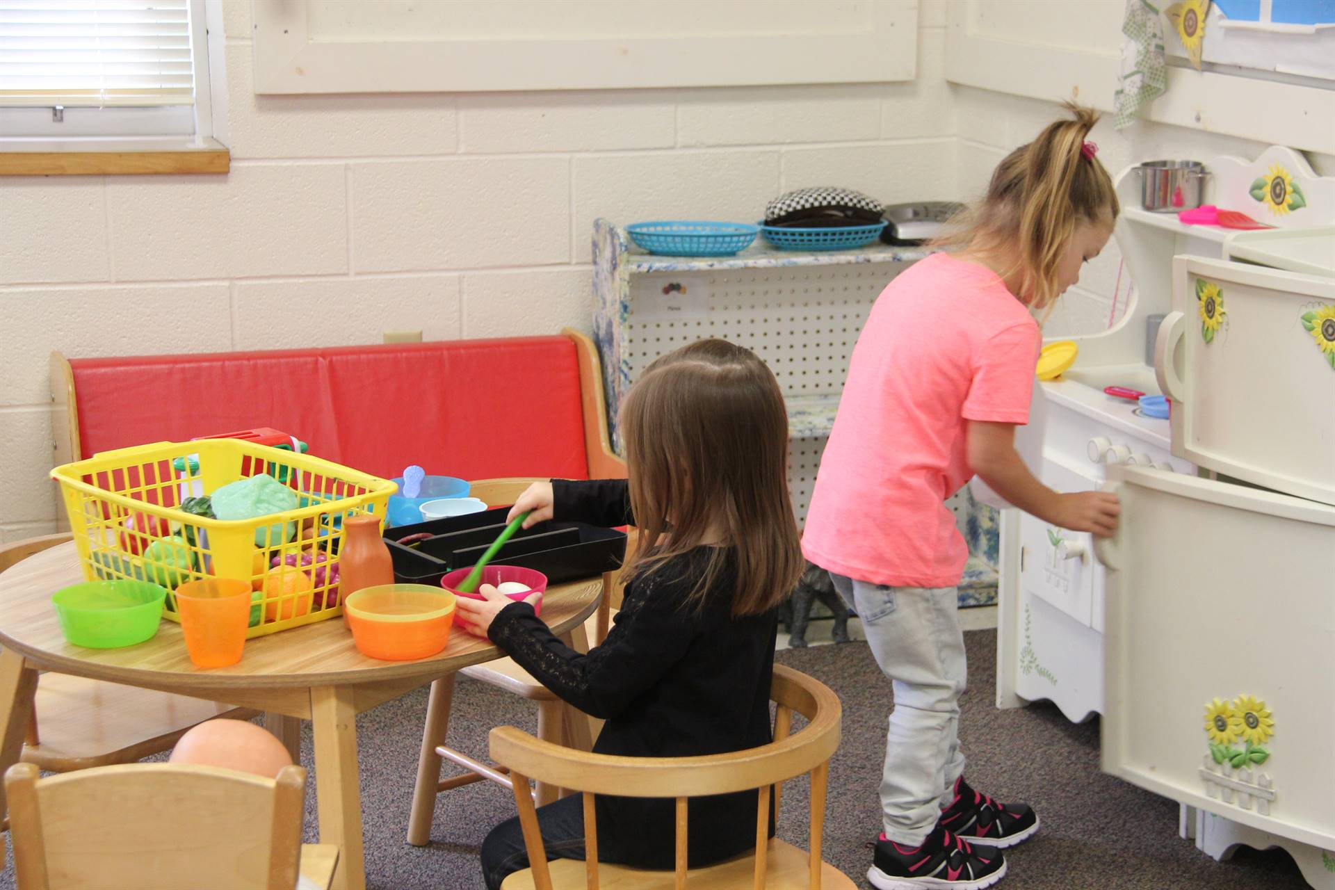 pre k students play in toy kitchen