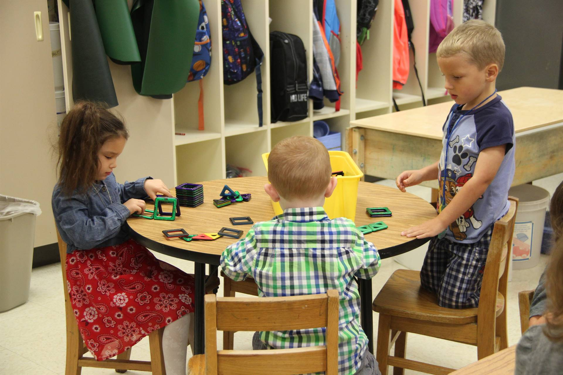 three pre k students play with blocks on first day