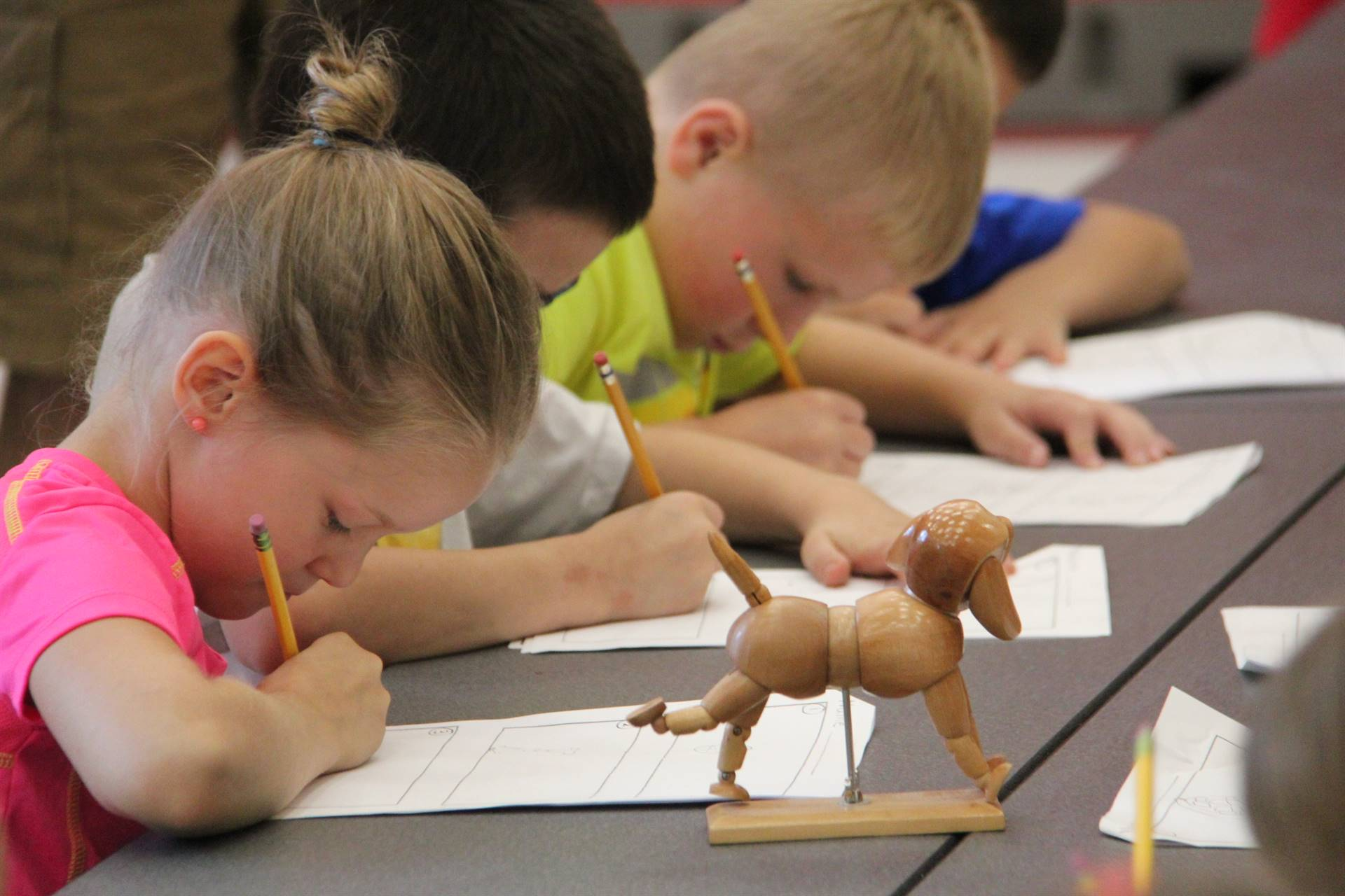 students sketch wooden dog