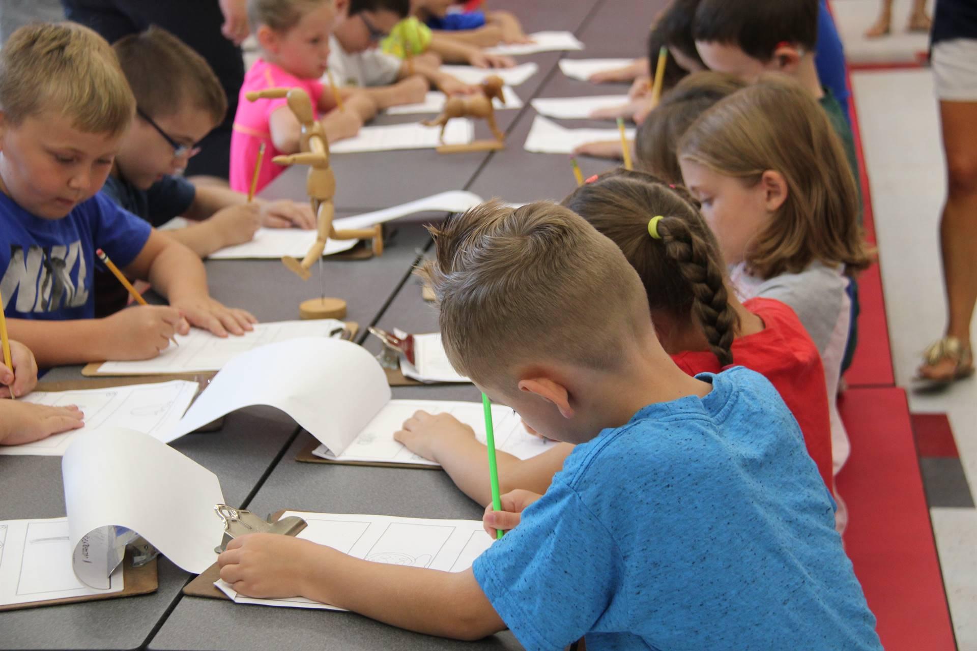 students sketch wooden figure