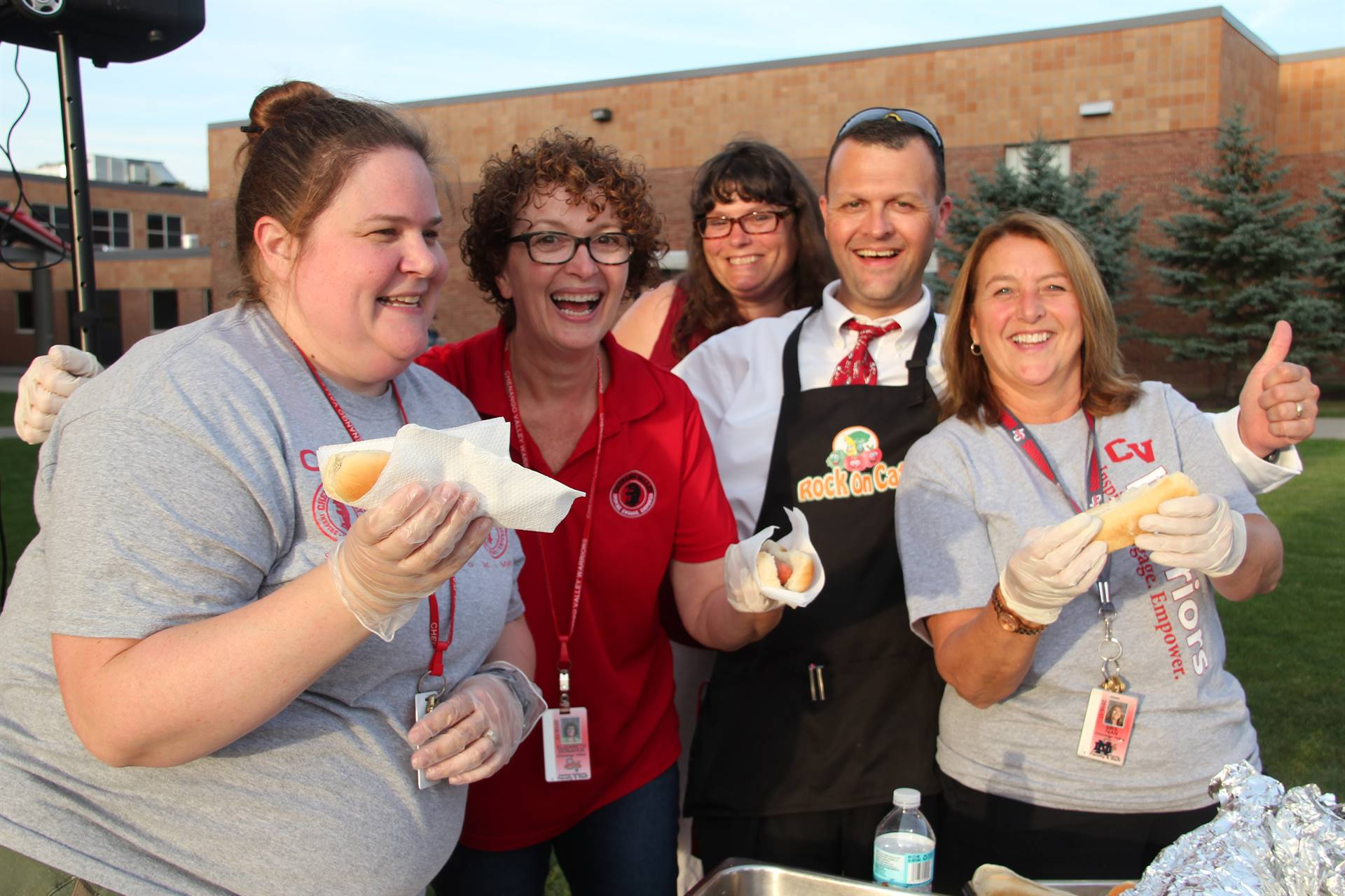c v staff members who are helping to serve hot dogs smile for a picture