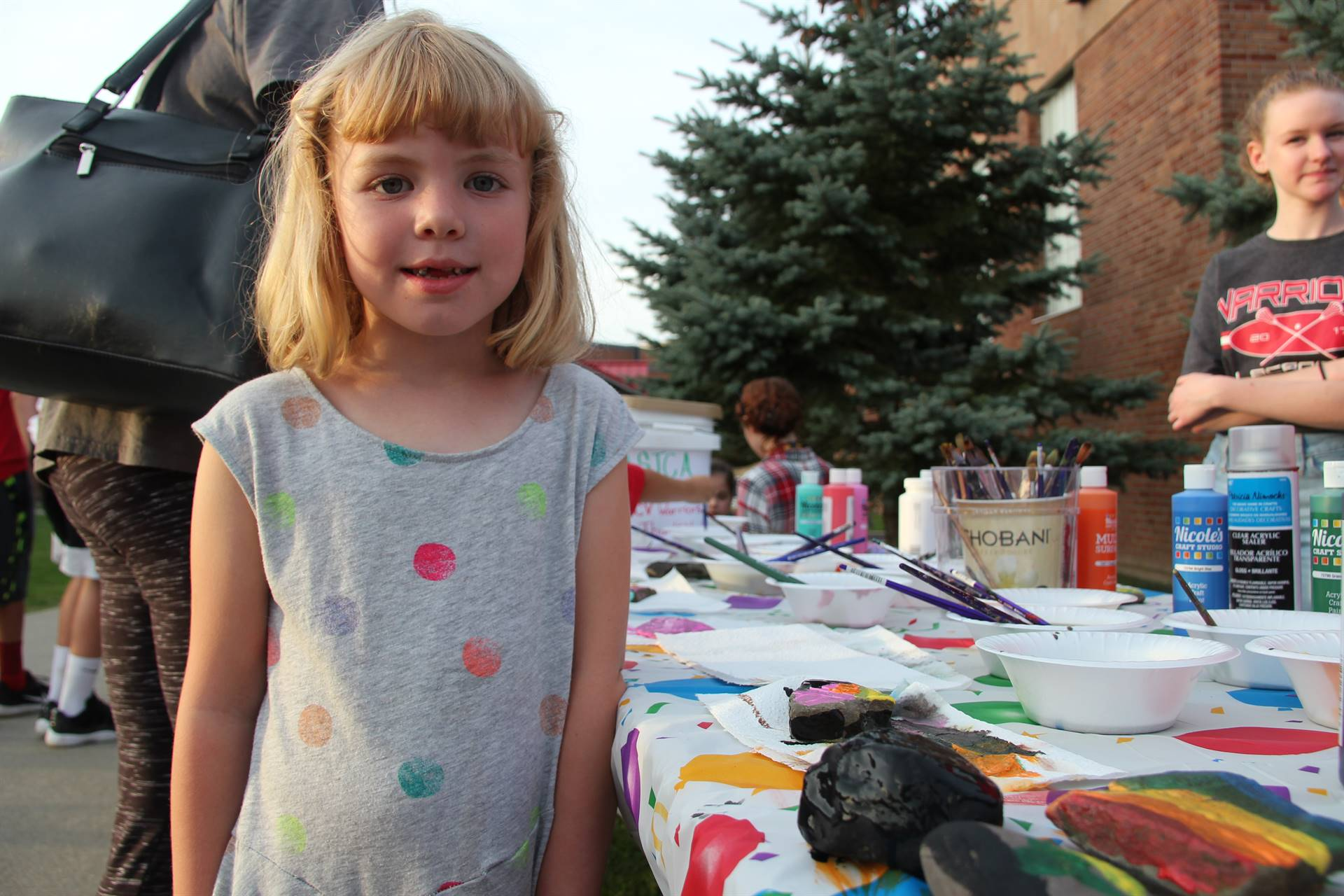 girl smiles next to rock she painted
