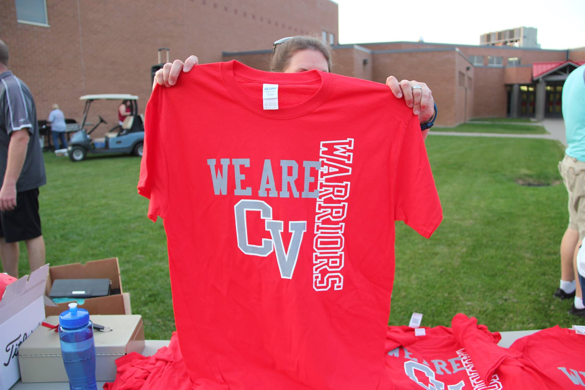 person holds up example of red rally in the valley tee shirt