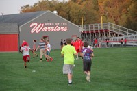 students playing in the field by the warrior stadium at rally in the valley