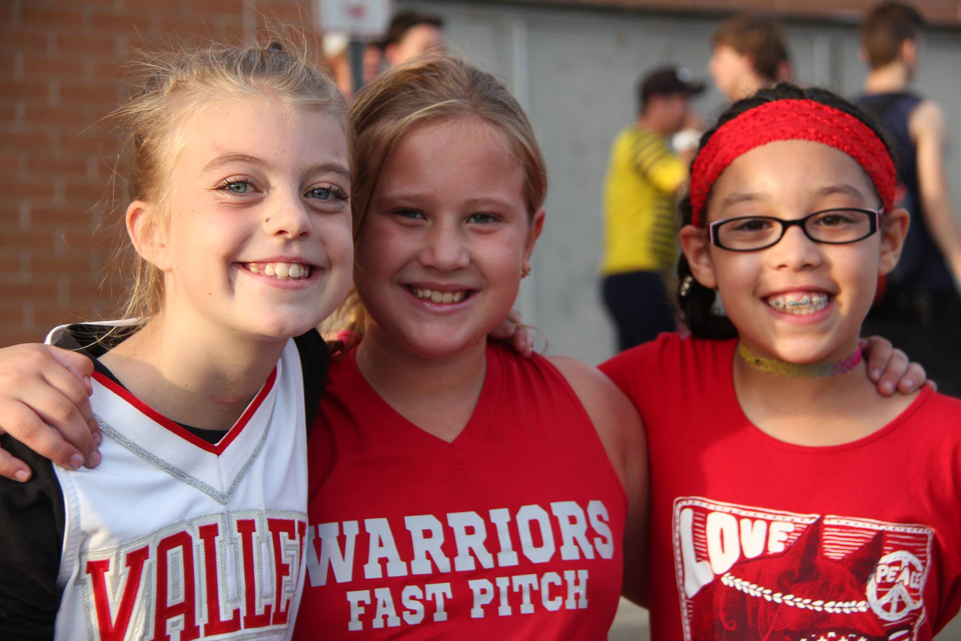 three girls smile for a picture at rally in the valley
