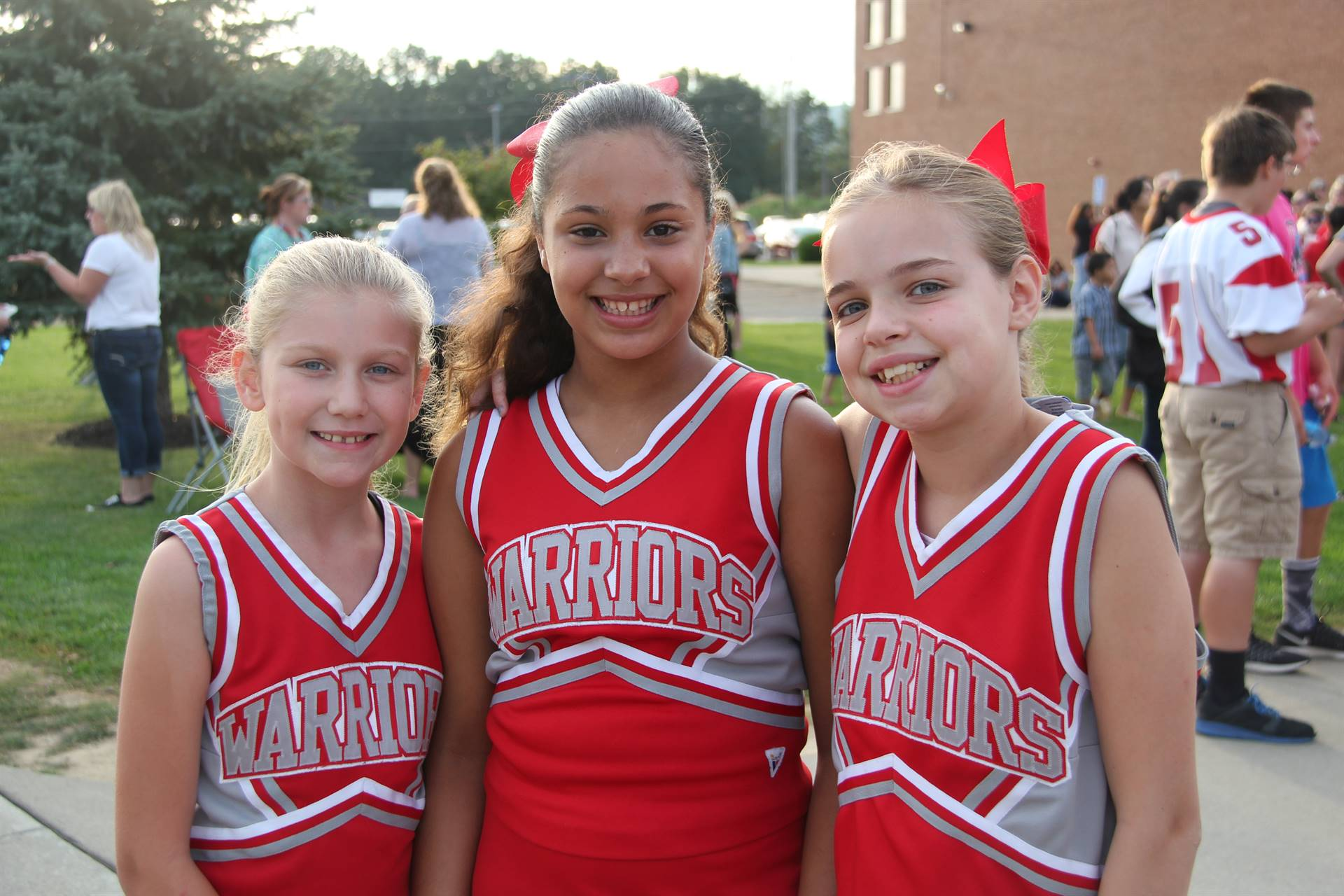 three warrior cheerleaders smile