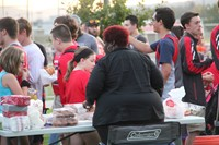 wide shot of c v staff member helping to serve donuts at rally in the valley event