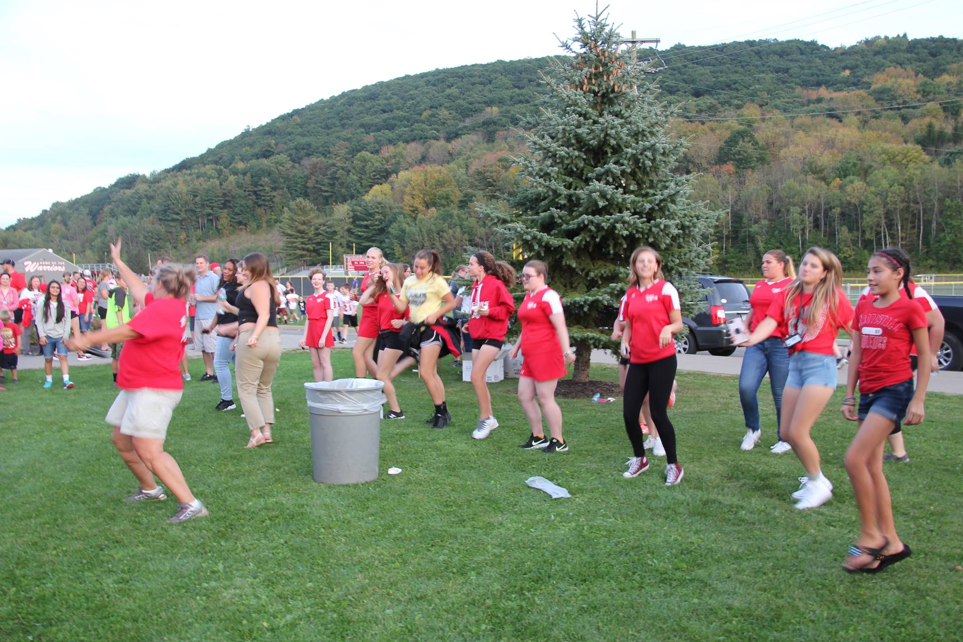 wide shot of students and teacher dancing at rally in the valley event