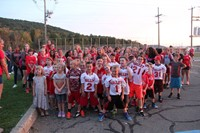 wide shot of students wearing jerseys listening to instructions for large group photo